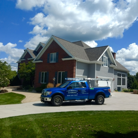 House with new roof, Performance Exterior Truck in foreground